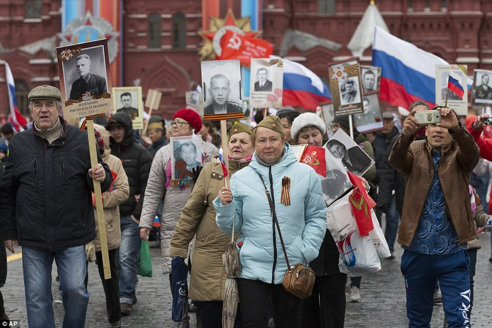 People carry portraits of relatives who fought in World War Two, and Russian and Soviet flags, during the Immortal Regiment march along the Red Square in Moscow