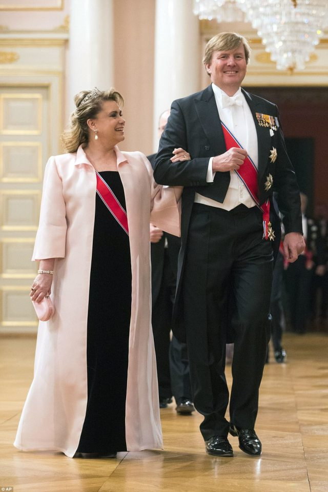 King Willem-Alexander of the Netherlands and Grand Duchess Maria-Teresa of Luxembourg smile as they walk arm in arm. The Dutch King's wife Maxima was also in attendance, but she entered the ballroom separately