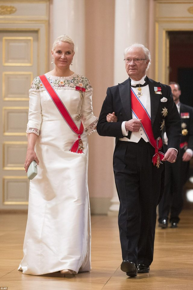 King Carl Gustaf of Sweden and Crown Princess Mette-Marit of Norway link arms as they enter the palace's celebrations. The Norwegian Princess looked stunning in a sweeping white gown with colourful floral detail around the collar