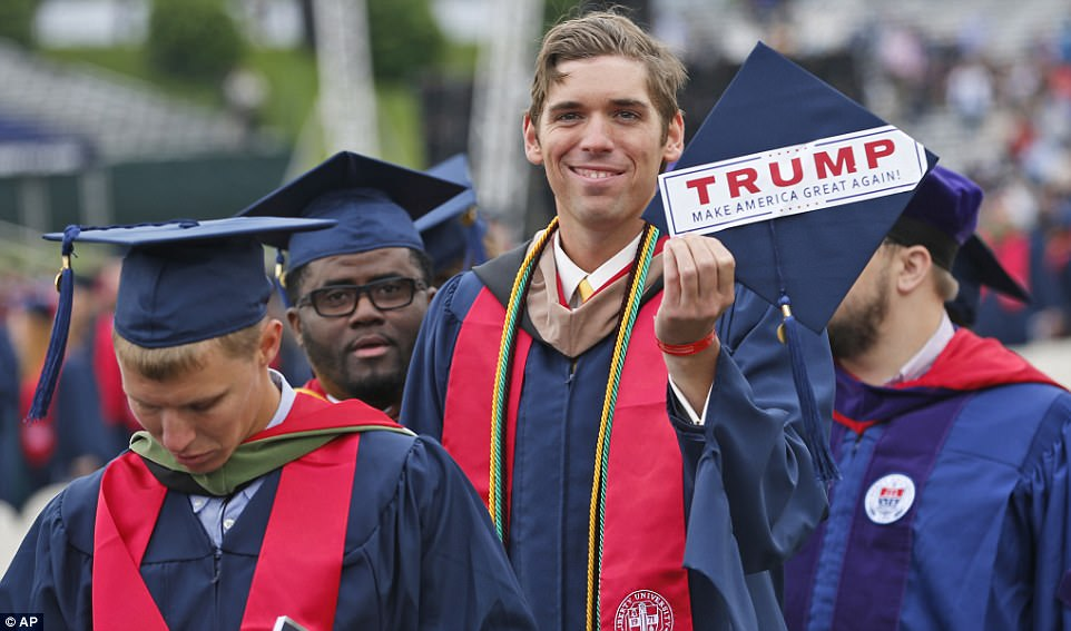 Liberty University graduate, David Westcott Jr displays a Trump sticker attached to the top of his mortar board as he walks into the stadium with other graduates at the start of commencement ceremonies