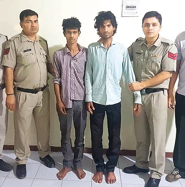 Sumit Kumar and his associate Vikas allegedly abducted the woman, and gang-raped and tortured her. The two men are shown between two police officers after their arrest