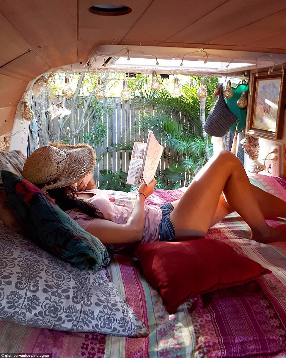 A free-spirited 'vanlifer' relaxes in her van and reads a book as afternoon sunlight beams through