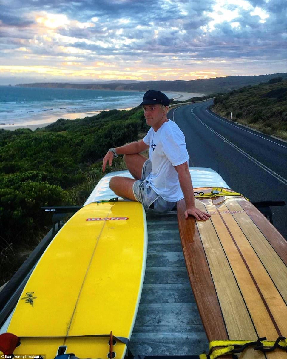Victorian man Liam poses on the top of his custom-made van with two surfboards as he travels towards Lorne