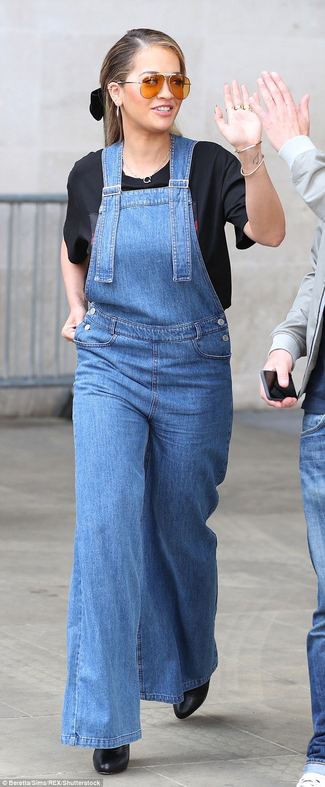 Don't leave her hanging! Rita Ora high-fives a by-passer as she struts into Radio One in baggy denim dungarees