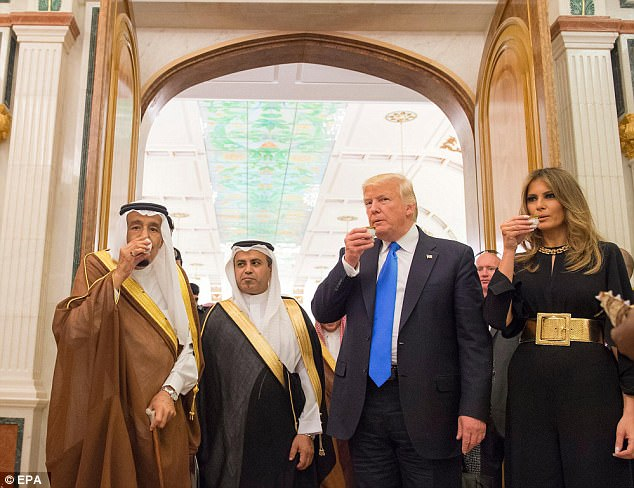 Donald Trump and wife Melania, dressed in a black jumpsuit with statement belt, sip a drink as they are welcomed by the Saudi king