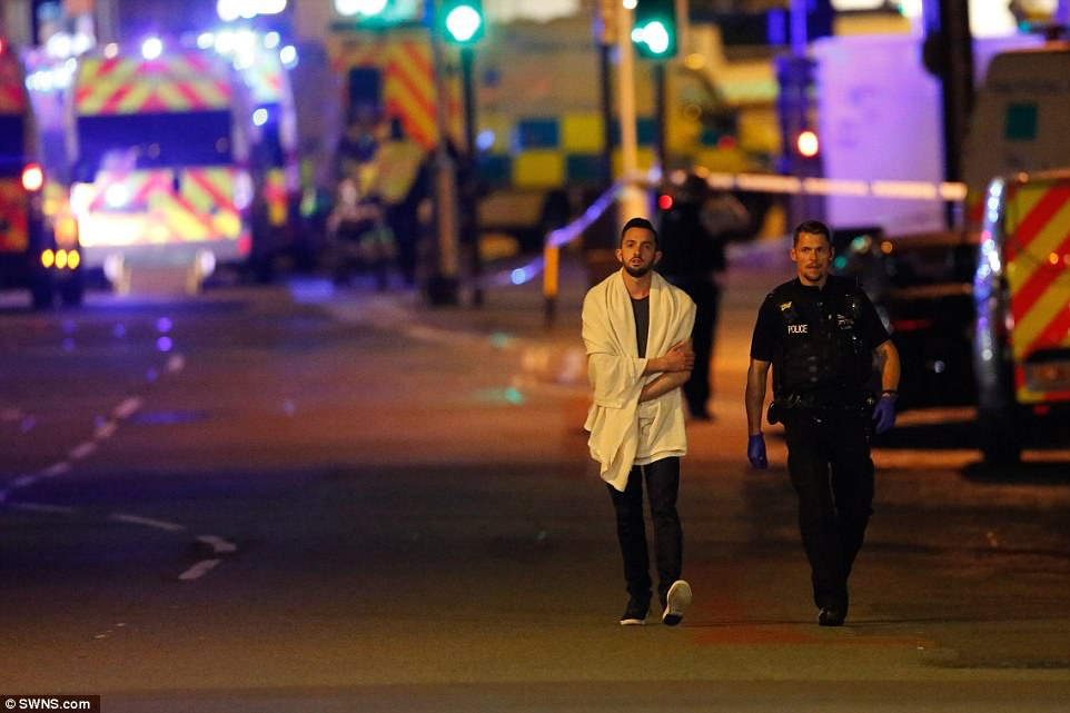 A man wearing a white towel walks next to a police officer.Concertgoers affected by the suspected terror attack  have been offered shelter by locals