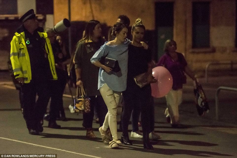 Two women support each other as they walk away from the concert venue. The pink balloon being carried is a reminder of the huge number of children who attended the performance