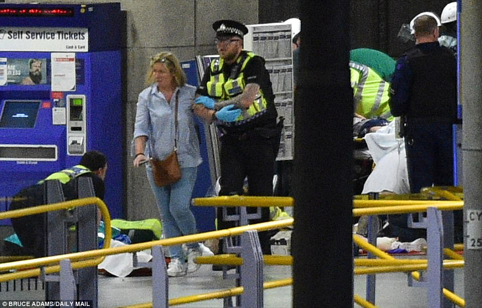 It is unclear where exactly the blast occurred, but initial reports indicated it happened either just outside the Manchester Arena or near a foyer. Pictured: Police help an injured woman in Victoria Station