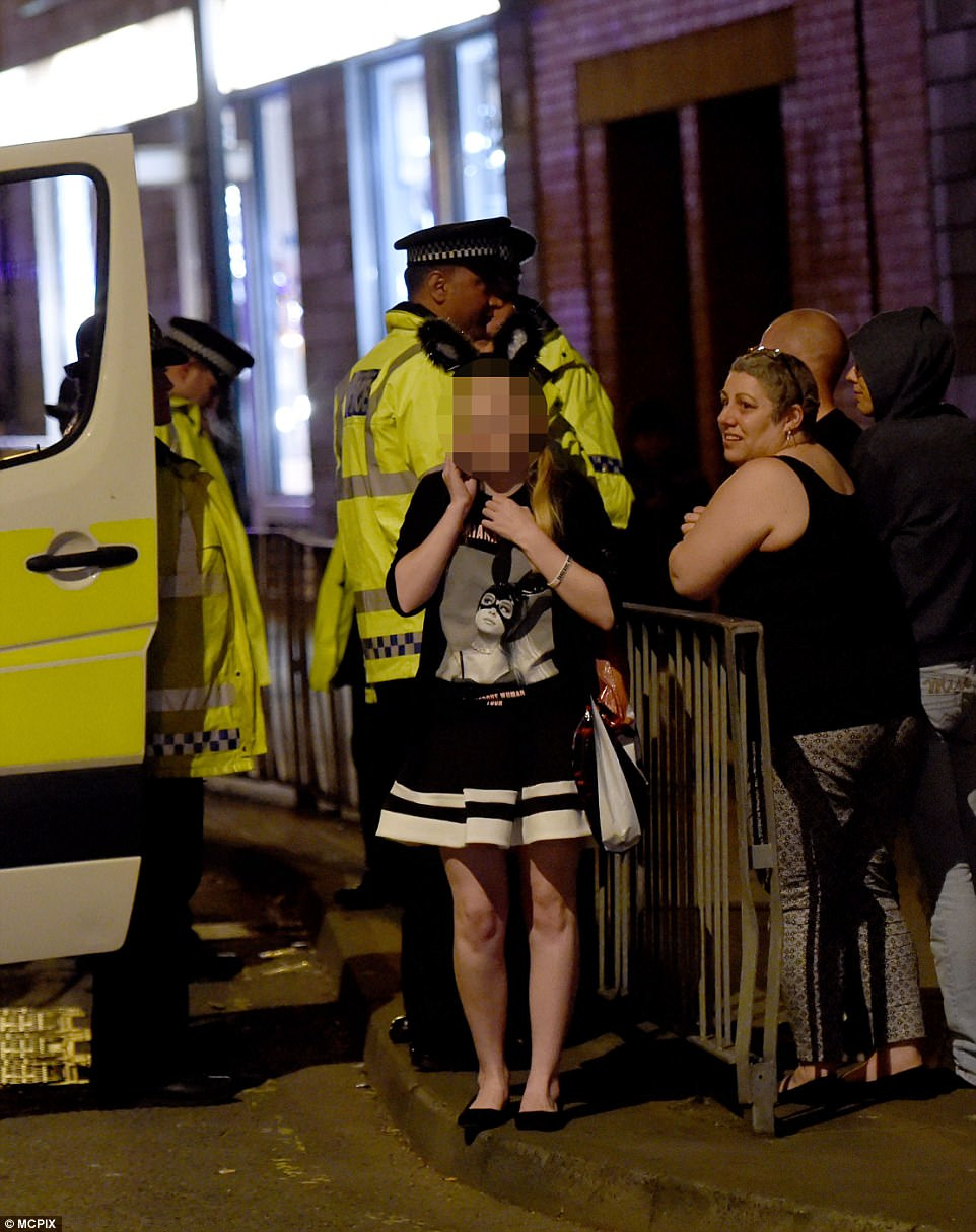 Grande, who was not injured, tweeted hours after the incident: 'Broken. From the bottom of my heart, I am so so sorry. I don't have words.' Pictured: A girl on the phone next to a group of police
