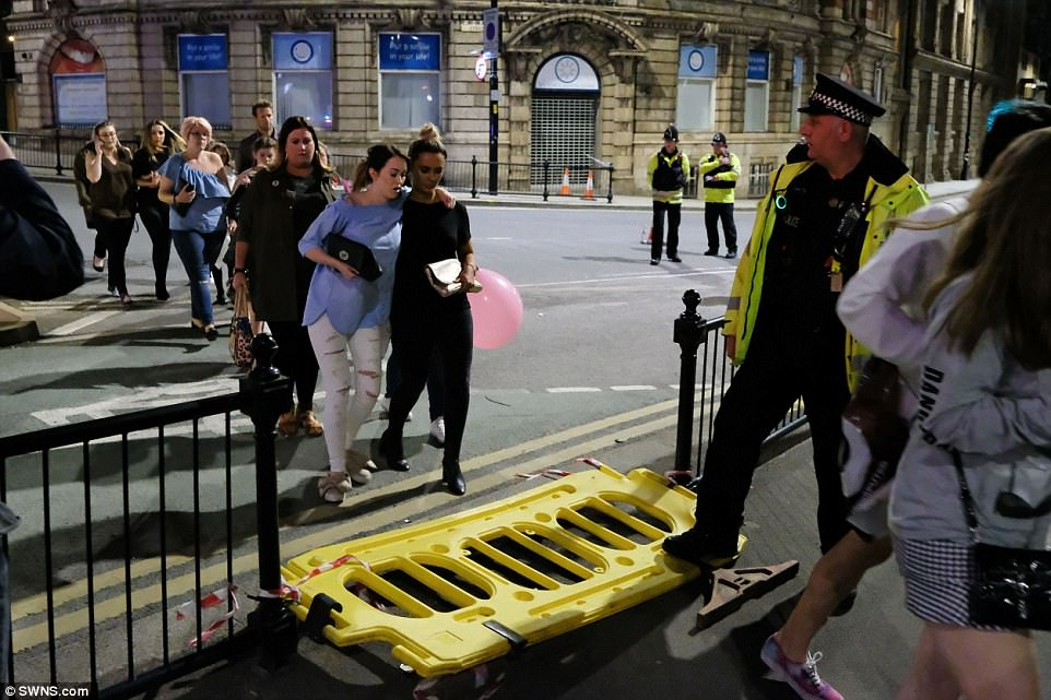 Police shut down the streets around the concert hall in the aftermath of the attack. Here, a group of women walk over a plastic barrier held down by a police officer