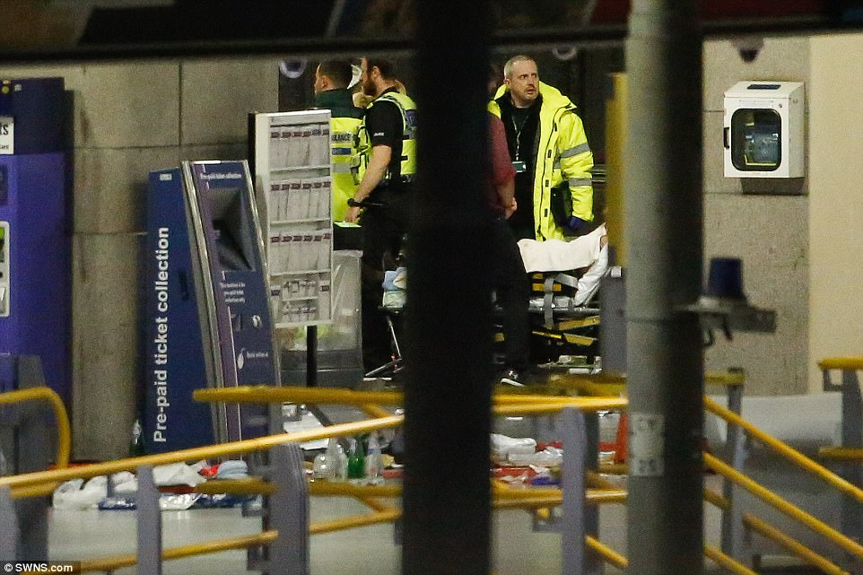 """Sir Richard Leese, leader of Manchester City Council, said: """"This is an absolutely horrifying incident and our thoughts are with everyone affected.' Pictured: Paramedics wheel away a casualty inside Piccadilly Station"""