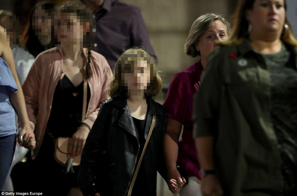 Manchester Arena said on its website that the blast struck outside the venue as concertgoers were leaving. Pictured: Children holding hands walking away from the scene