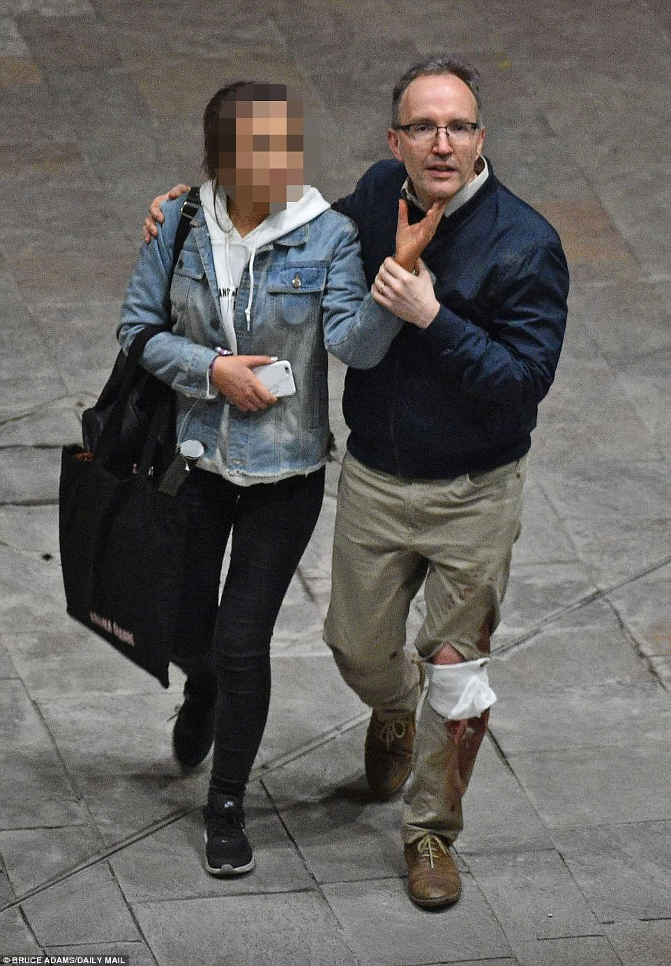 A man with an injured legs guides a teenage girl outside of the venue following the blast, the cause of which has not been determined for certain