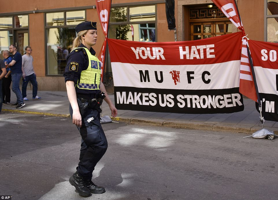 A police officer walks past another banner which reads 'Your hate makes us stronger'