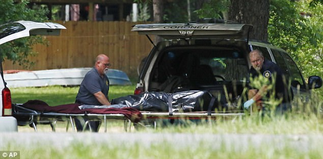 Pictured, officials removing a body from one of the crime scenes in Brookhaven, Mississippi on Sunday