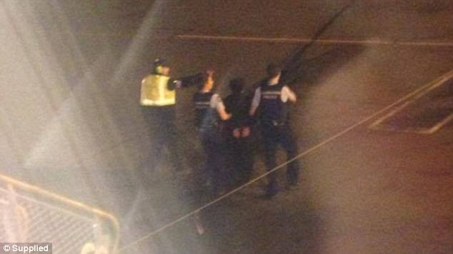 An image of from one of the windows on the plane show Kiri Marsh being escorted away by two police officers assisted by airport security