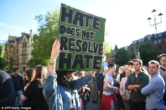 Una mujer sostiene un cartel que dice 'El odio no resuelve el odio' durante una vigilia en Albert Square en Manchester el día después del ataque Arena