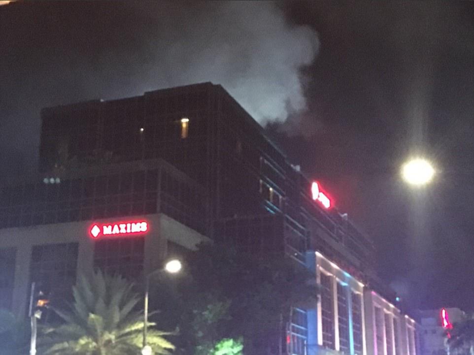 Una multitud de personas corrieron desde el complejo como el humo se elevaba desde el techo de uno de los edificios