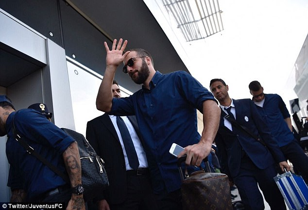 Higuain waves to the media and supporters after arriving after at the airport in Italy on Friday