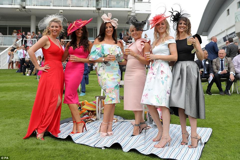 Negrito e brilhante: seis amigos vestiram-se com elegantes vestidos de moda em tons de vermelho, fúcsia e pêssego enquanto desfrutavam um pouco de vinho ao sol