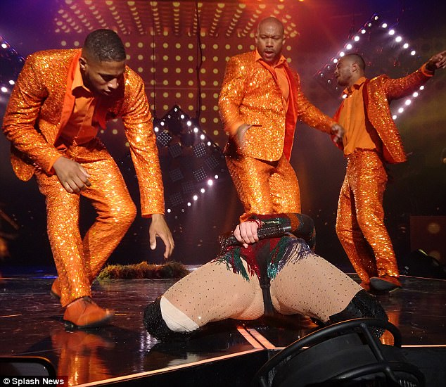 Ouch: The 47-year-old was literally bent over backwards mid-song when her backing dancers rushed over to hoist her back the right way up