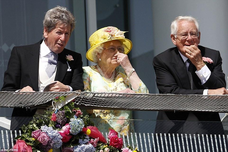 A rainha foi vista de pé em uma varanda com o seu conselheiro de corrida John Warren (à esquerda).  O Sr. Warren é uma figura líder no mundo das corridas de cavalos que supervisiona todos os interesses de raça e de criação de cavalos da Rainha