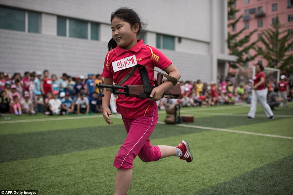 A girl carrying a mock rifle completes an obstacle course at games marking 'Children's Union Day', in Pyongyang this morning