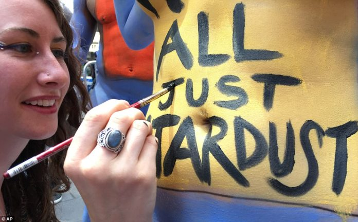 Artists, like Caren Charles (pictured) painted hundreds of nude models with messages meant to inspire 'positivity and acceptance' during New York City artist Andy Golub's latest public body painting exhibit, 'Body Notes,' on Friday