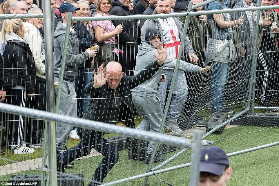 EDL manifestantes tratan de derribar las barreras impuestas para separarlos de manifestantes antifascistas