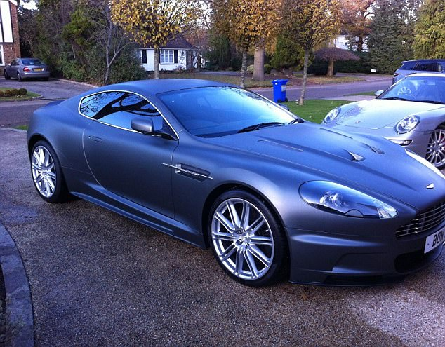 The Rydon CEO has an Aston Martin with a private 'Bond' number plate pictured here next to the family's silver Porsche