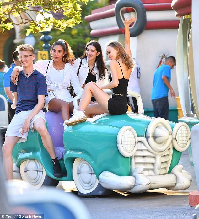 Having a ball: The 18-year-old model and her friends all perched themselves on a turquoise false car that's been set up near a themed rest stop called Goofy's Gas Station