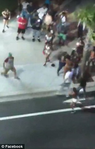 Video captured a man in a white T-shirt (pictured on the sidewalk) pull out a gun and shoot the others