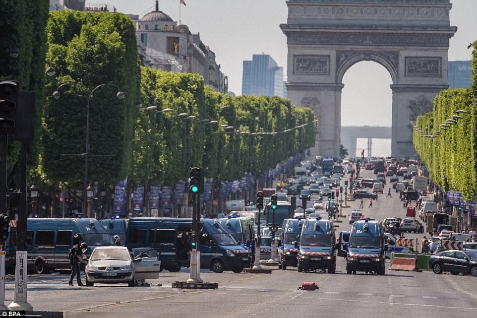 La izquierda automóvil abandonado en la avenida de fama mundial y un bote de color rojo se puede ver en el medio del camino que está lleno de policías