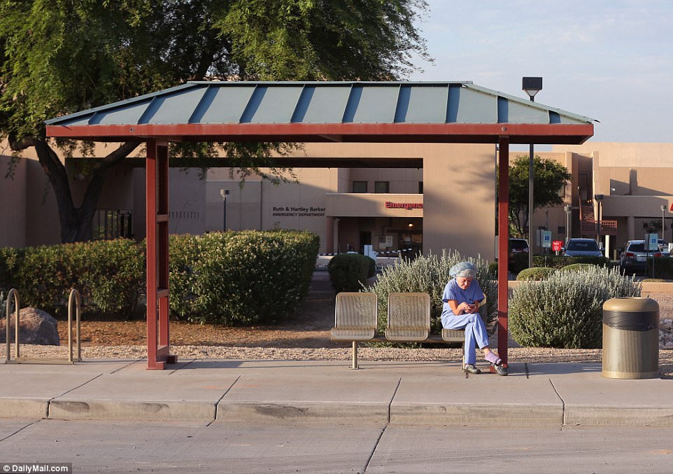 Above a hospital worker in Phoenix takes a break outside  Tuesday morning in a bid to beat the extremely warm weather