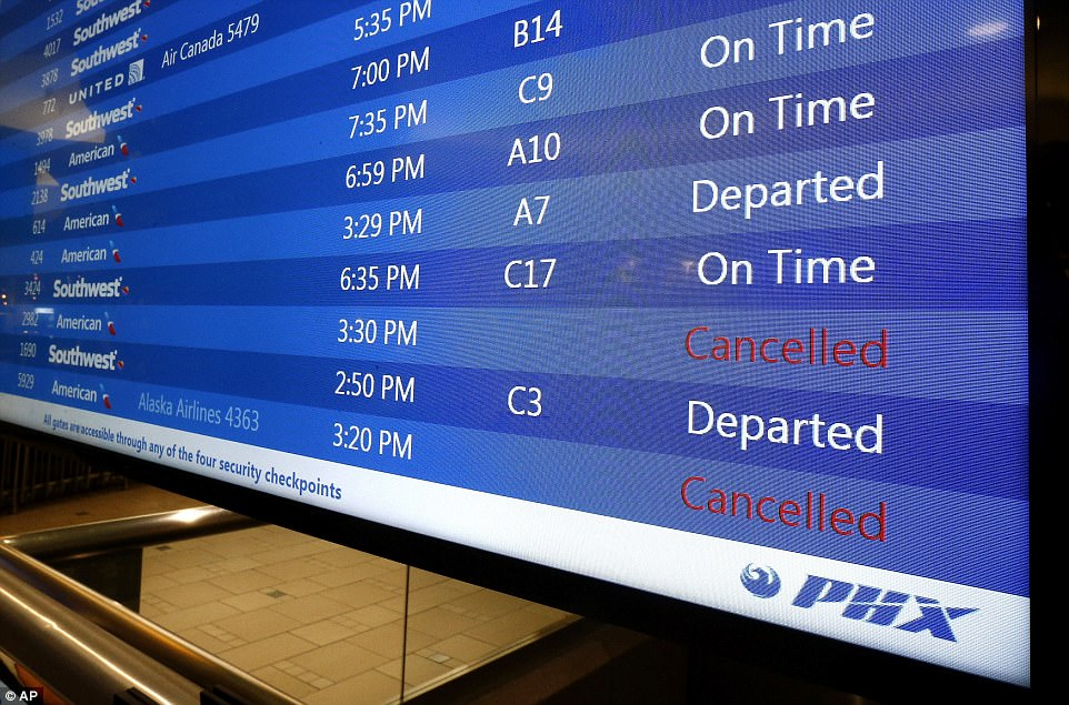 At Phoenix Sky Harbor International Airport, departure signs show regional jet cancellations. American Airlines says seven regional flights have been delayed and 43 have been canceled because of the heat wave