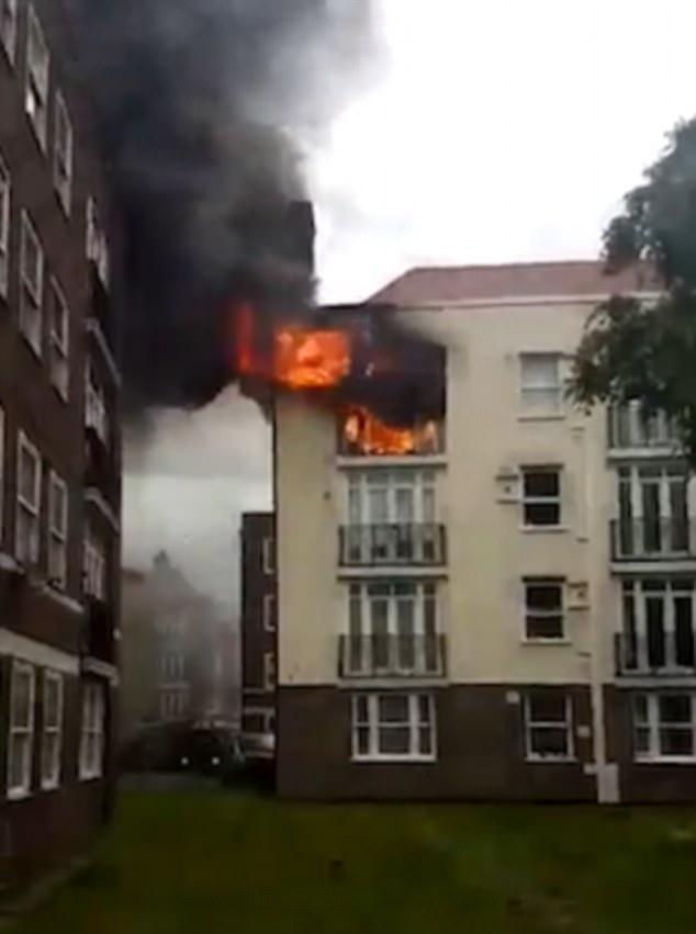 Las llamas de las ventanas con espesa nube de humo negro en el cielo por encima de la calle de Turín