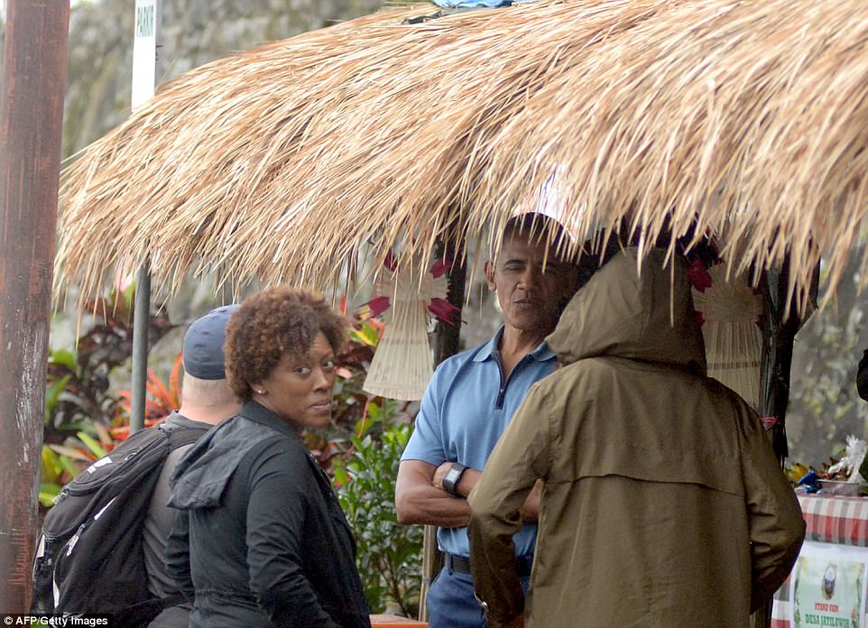 Obama appears to be chatting to Michelle (right) during the trip to the rice fields