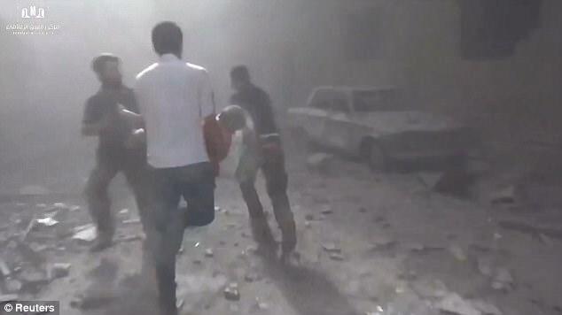 Uno de los hombres sprint por la calle, que está llena de escombros, con un niño herido en sus manos