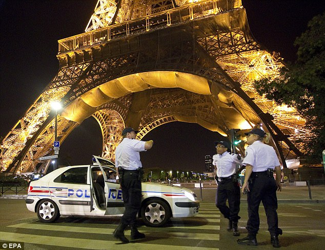 French police officers and security personnel stand guard at a security cordon around the Eiffel Tower