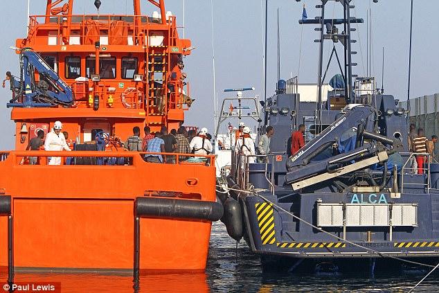 La guardia costera (izquierda) ayudó a traer a inmigrantes que acababan de ser rescatados cerca de la costa de África del Norte