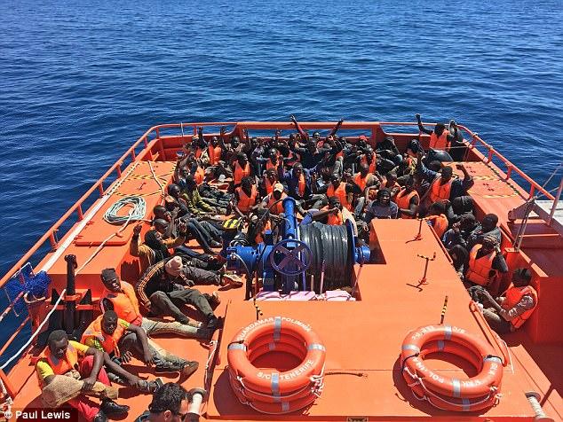Algunos de los migrantes en el barco puso sus brazos en el aire después de ser rescatado cerca de España