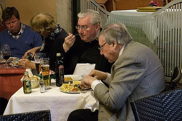 Cardinal George Pell is expected to be charged over child sex abuse allegations (pictured eating in Italy)