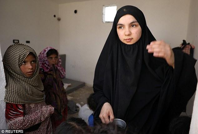 Las niñas miran libanés Nour Al-Huda, esposa de un ex combatiente de Estado Islámico, en un campamento para personas desplazadas en Ain Issa, al norte de Raqqa, Siria