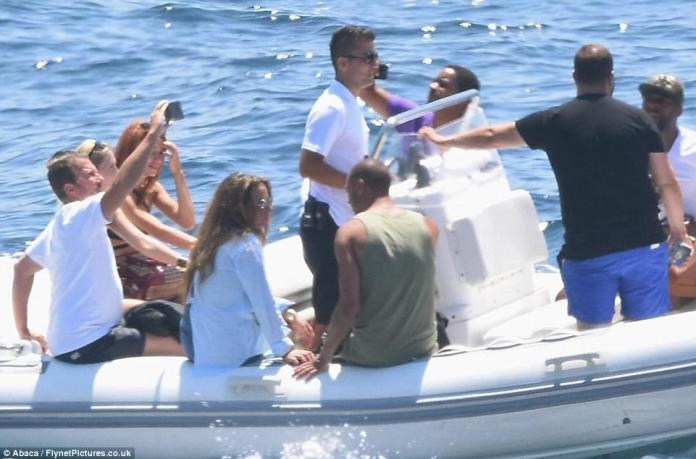 The pair sat side by side, looking deep into one another's eyes as members of their entourage took selfies on the dinghy that ferried them back to their yacht