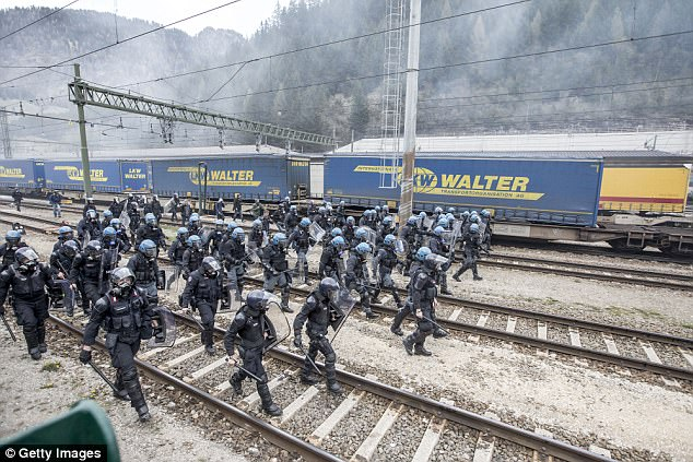 Riot police walk along the railway tracks during a rally against the Austrian government's planned introduction of border controls at Brenner Pass in May last year