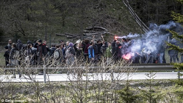 Flares are set off during a protest against the introduction of border controls in Austria in 2016