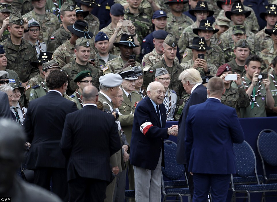 Donald Trump shake hands with veteran as dozens of other slook on after delivering a speech in Krasinski Square in Warsaw, Poland on Thursday