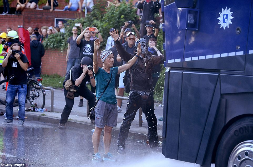 Pictured: Two people stand in front of an armoured police vehicle with their hands up