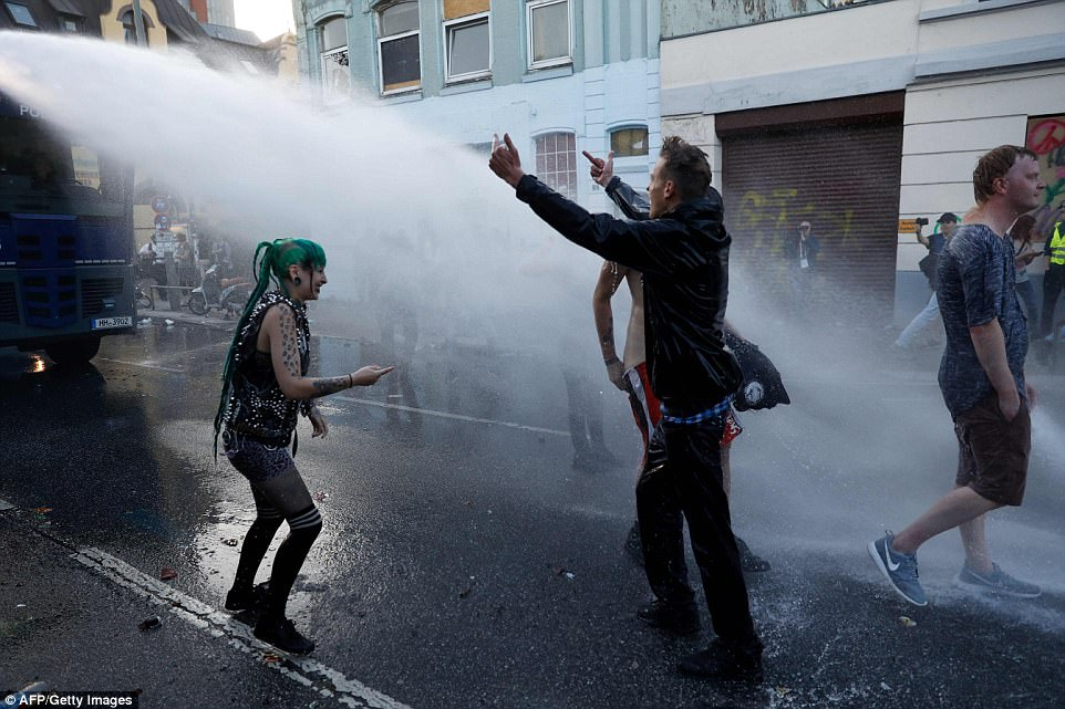 Pictured: A protester gestures defiantly towards a police riot van as it sprays him with water