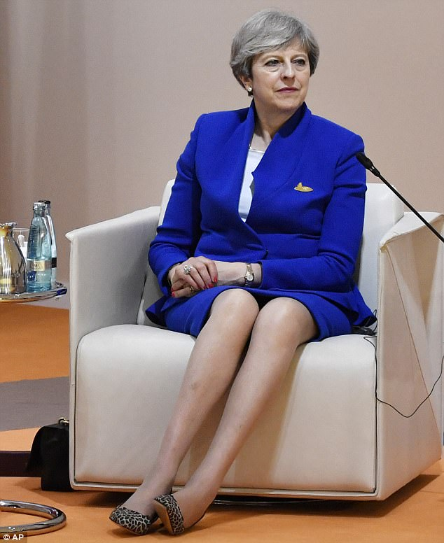 Theresa May (pictured at the G20 summit in Hamburg today) has insisted the target of spending 0.7 per cent of national income on aid will stay in place